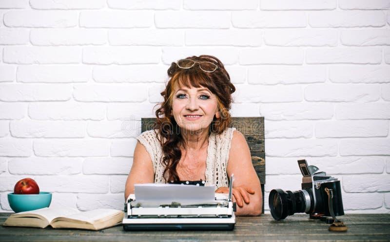 copywriter Hög författare på skrivbordet Arbete för gammal kvinna i författarekontor Hög kvinnatyp på den retro skrivmaskinen jou royaltyfri foto