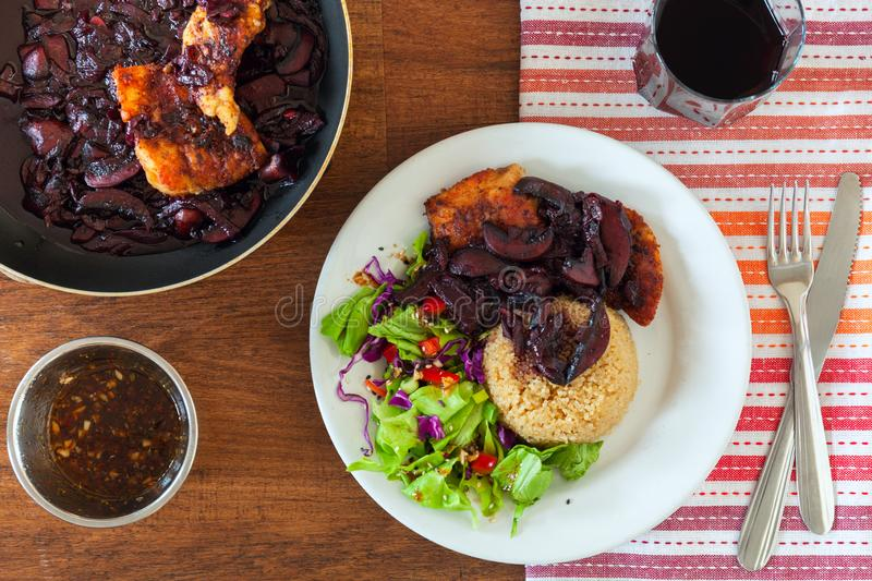 Coq au vin chicken. braised with wine - French. French dish of chicken braised with wine. The dish is decorated with. Fresh salad and served with quinoa. Stock royalty free stock photos