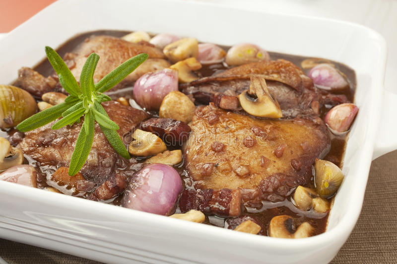 Coq au Vin Chicken in Red Wine. French classic, coq au vin or chicken in red wine with mushrooms, onion and bacon. Perfect for Sunday lunch with mashed potato royalty free stock photography