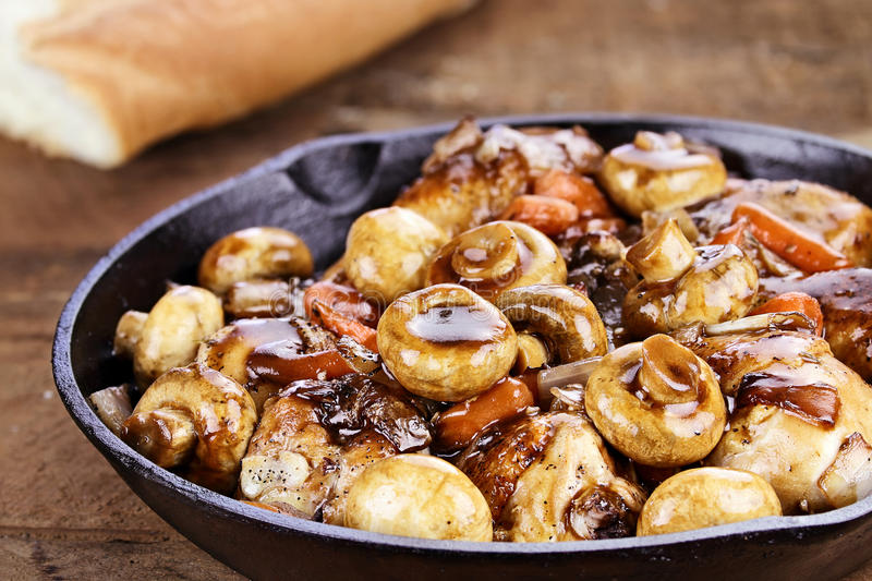 Coq Au Vin. In rustic cast iron pan with shallow depth of field stock photos