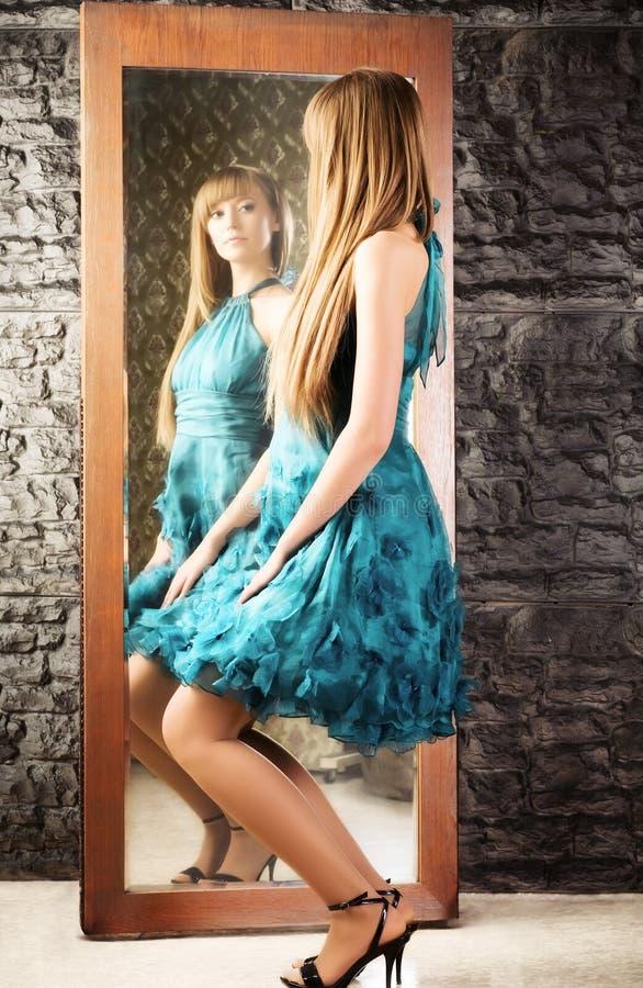 Coquet Frau vor dem Spiegel stockbild