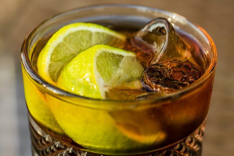 Coquetel alcoólico - Chá Forçado de Longa Ilha Chá gelado com limão em vidro, close-up Uma bebida doce marrom imagem de stock royalty free