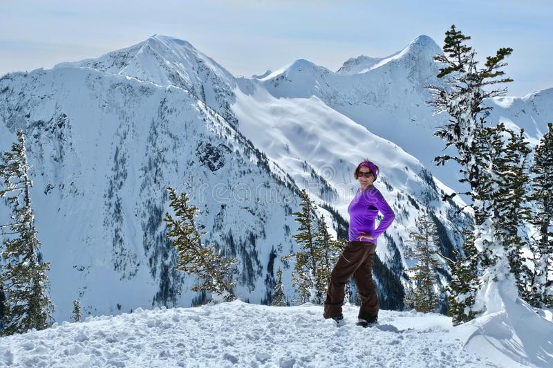 Senior woman snowshoeing in mountains near Vancouver. royalty free stock photography