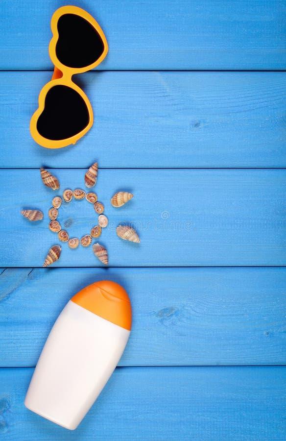 Coquillages dans la forme du soleil, des lunettes de soleil et de la lotion du soleil sur les panneaux bleus, accessoires pour l' image libre de droits