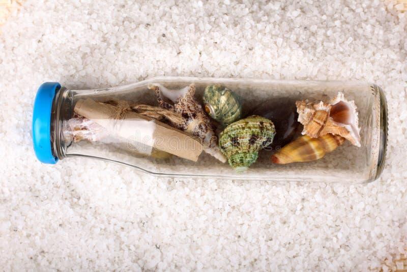 coquillages dans une bouteille sur un fond de sel de mer photo libre de droits
