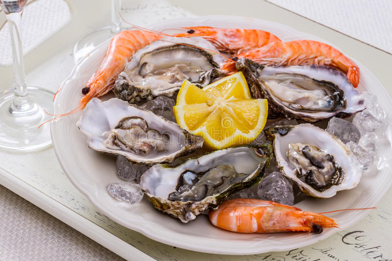 Coquille d'huîtres, crevette enorme avec le citron sur la glace image stock