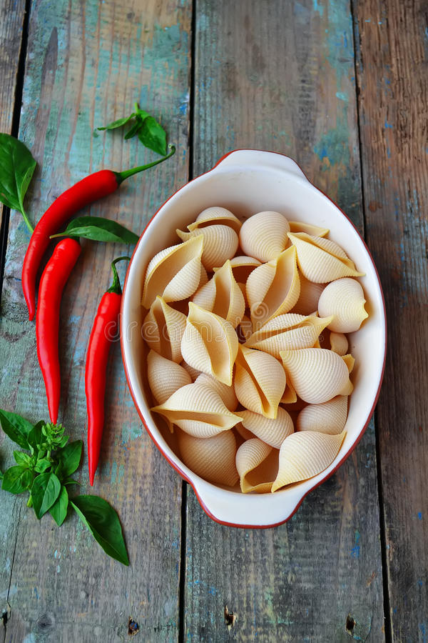 Coquilles de pâtes en forme, poivre de piment et basilic en céramique sur un en bois photos stock
