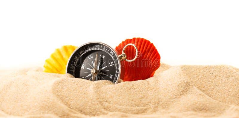 Coquilles et boussole de mer en sable photographie stock