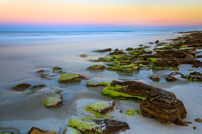 Coquina kamienia plaża przy zmierzchem obrazy royalty free