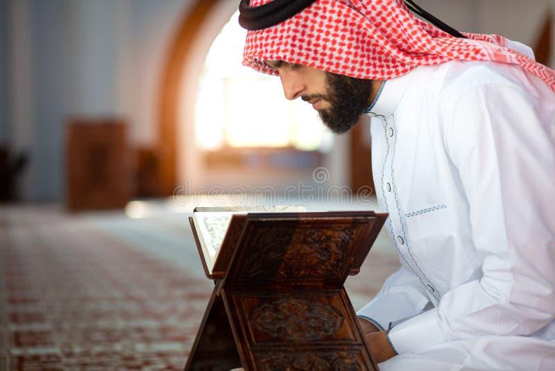 Corán étnico de la lectura del hombre y rogación en mezquita imagen de archivo