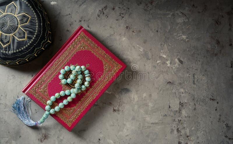 Corán con el rosario y rogar el sombrero en fondo gris de la pizarra Concepto islámico con el espacio de la copia, visión superio fotografía de archivo
