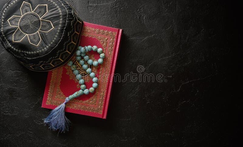 Corán con el rosario y rogar el sombrero en fondo negro de la textura de la piedra o de la pizarra Concepto islámico con el espac fotos de archivo