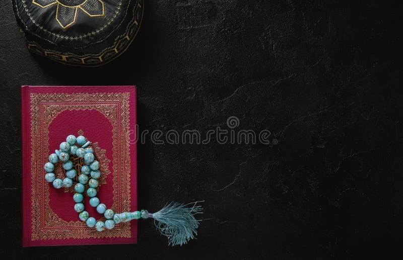 Corán con las gotas del rosario y sombrero musulmán en fondo negro de la textura de la pizarra Concepto islámico con el espacio d fotografía de archivo libre de regalías