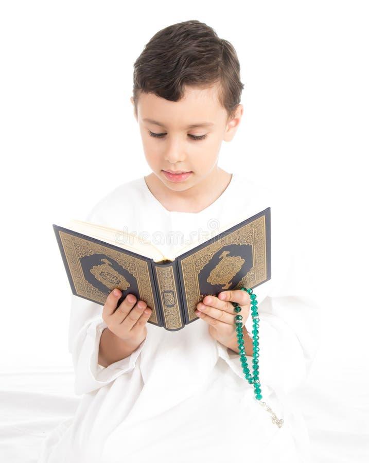 Corão da leitura do menino e rosário novos muçulmanos da terra arrendada foto de stock royalty free
