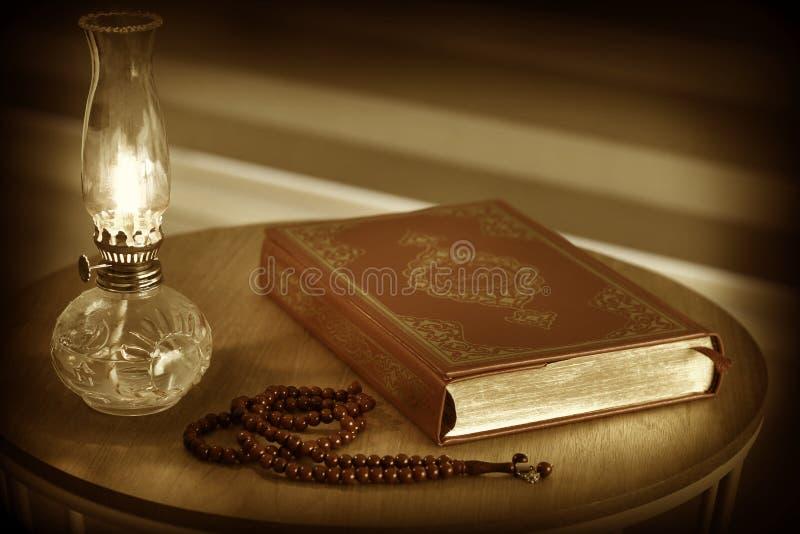 Corão, grânulos do rosário e lâmpada de óleo em um suporte de madeira fotografia de stock