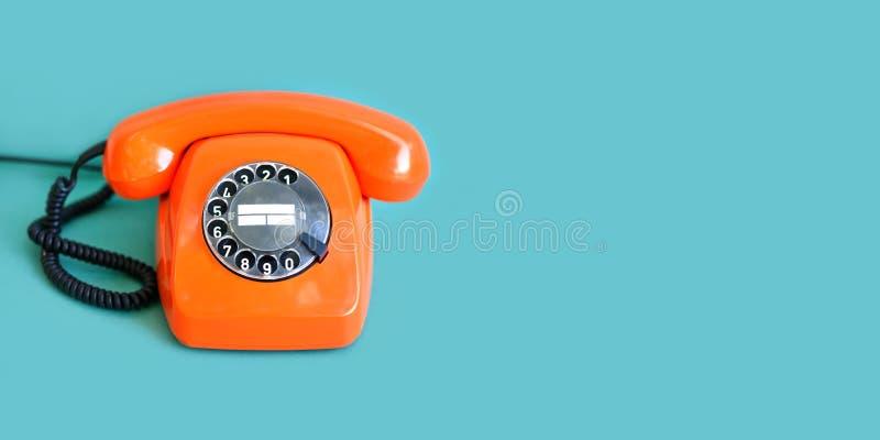 Cor alaranjada do telefone retro, receptor do monofone do vintage no fundo verde Copie o espa?o fotografia de stock royalty free