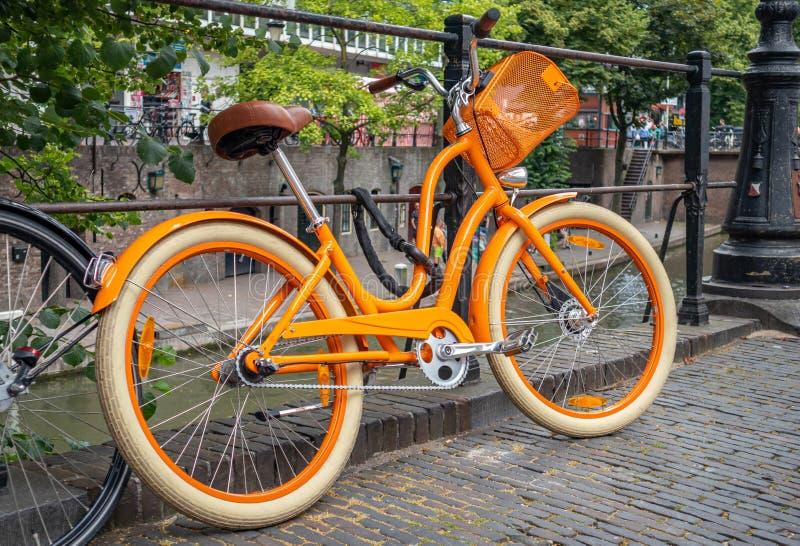 Cor amarela da bicicleta travada em um trilho do canal do rio na cidade de Utrecht, Países Baixos imagens de stock