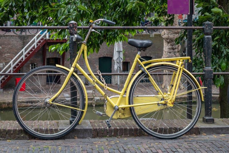 Cor amarela da bicicleta travada em um trilho do canal do rio na cidade de Utrecht, Países Baixos fotografia de stock