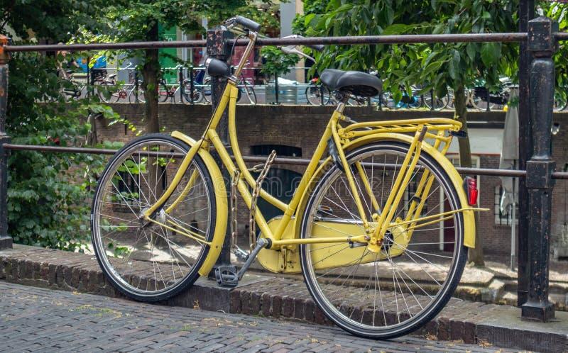 Cor amarela da bicicleta travada em um trilho do canal do rio na cidade de Utrecht, Países Baixos foto de stock
