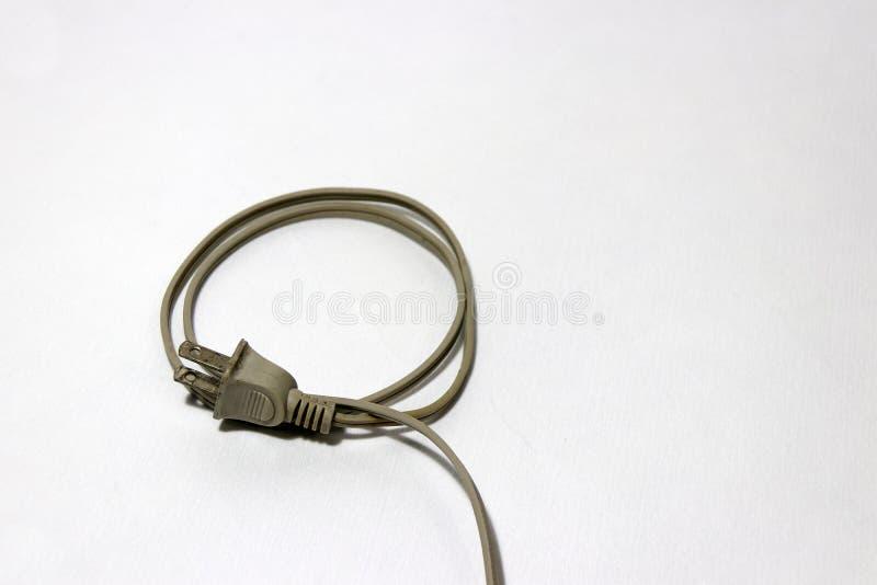 Cor de creme usada da tomada com o cabo enrolado sobre o assoalho branco Usado para a conexão elétrica foto de stock royalty free