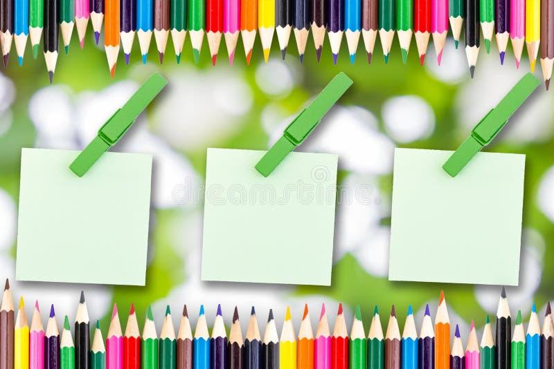 A cor de papel e a madeira grampeiam a nota no bokeh verde com lápis da cor imagens de stock royalty free