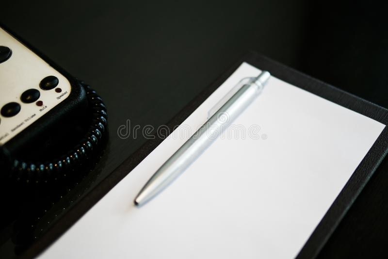 A cor de prata da pena é colocada no papel branco de nota sucinta na tabela de madeira marrom perto do telefone na sala de hotel  fotos de stock royalty free