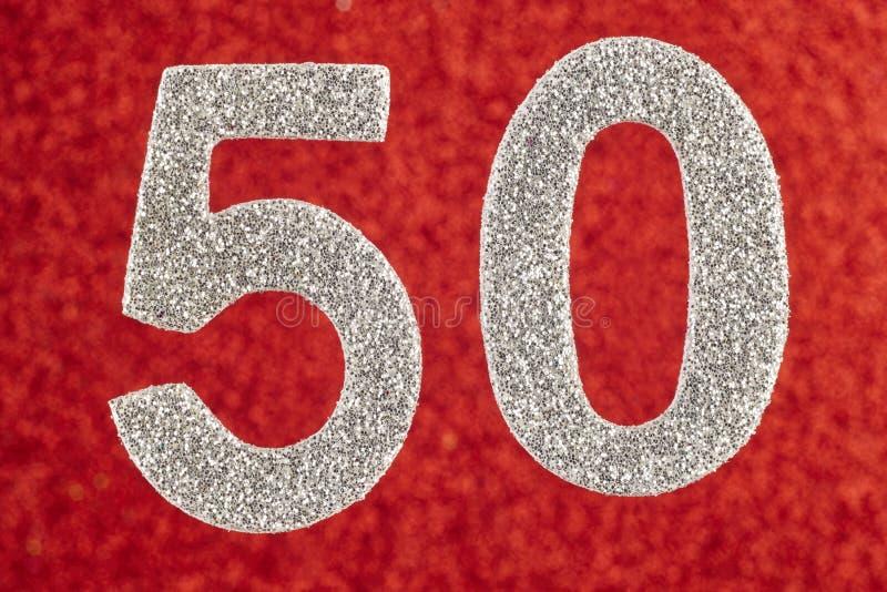 Cor de prata do número cinqüênta sobre um fundo vermelho anniversary fotografia de stock