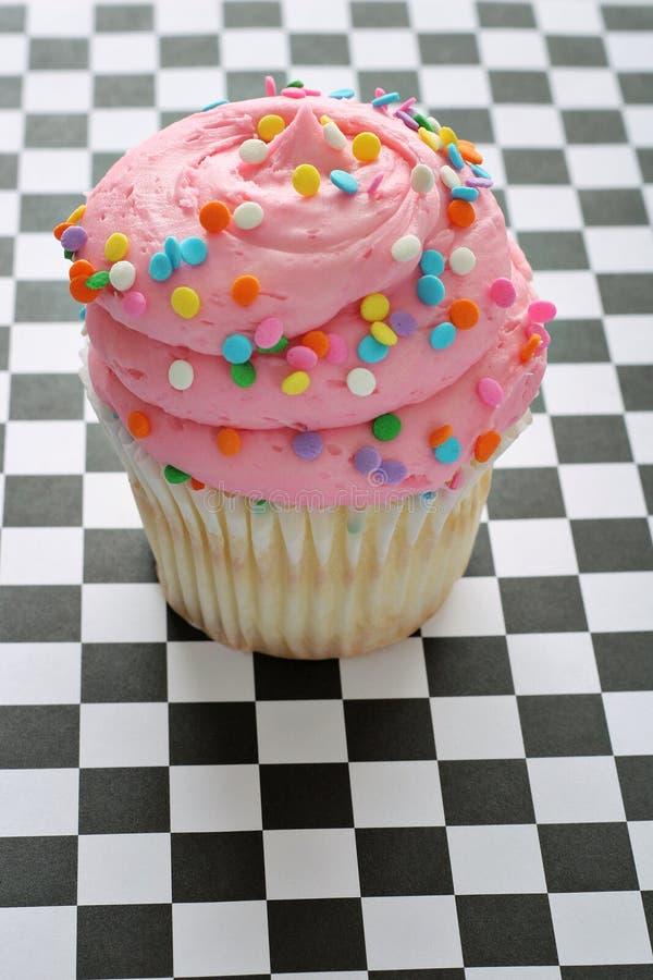 A cor-de-rosa polvilha o queque em fundo checkered imagens de stock royalty free