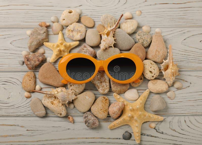 Cor e shell alaranjados dos óculos de sol, pedras do mar e uma estrela do mar sobre imagens de stock