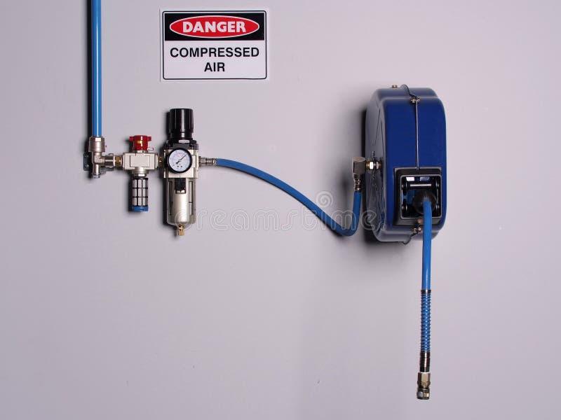 A cor fixa codificou a linha de ar comprimido com o regulador de pressão e flexivelmente o carretel da mangueira foto de stock