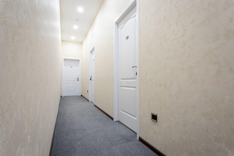 Cor leitosa iluminada do corredor com as três portas brancas e um teto branco Decorado em cores claras No tapete cinzento do asso fotografia de stock