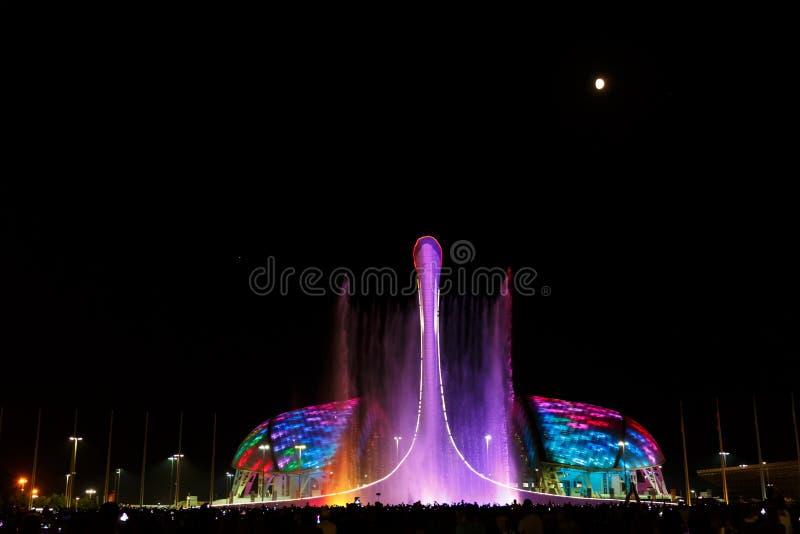 Cor, música, fonte na cidade de Sochi no fundo do estádio Fisht imagem de stock
