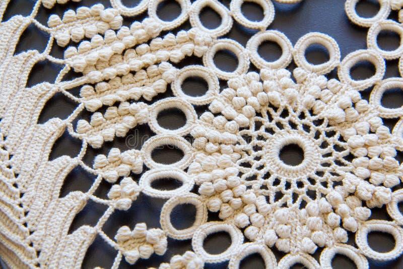 Cor natural o algodão mercerizado faz crochê a flor do vintage e o fim da toalha de mesa das folhas acima na tabela preta Projeto foto de stock