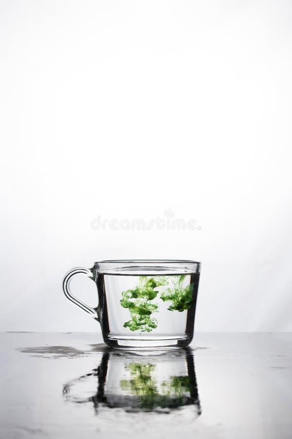 A cor verde dissolve-se em um copo de água em um fundo branco A caneca é refletida na superfície molhada Na parte superior há um  imagem de stock royalty free