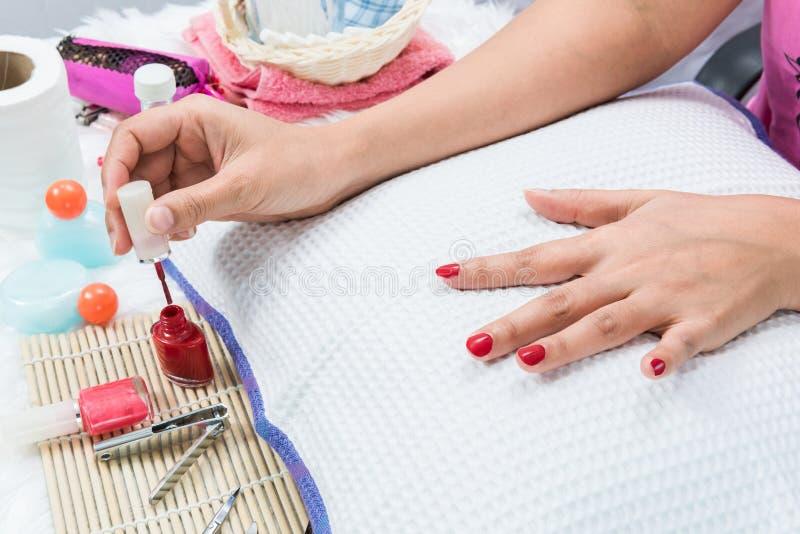 Cor vermelha da pintura do prego do tratamento de mãos foto de stock