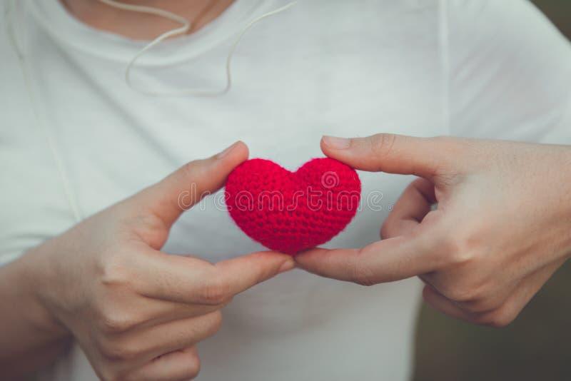 Cor vermelha do amor e do coração na mão das mulheres imagens de stock