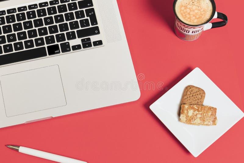 Cor vermelha do fundo moderno do negócio com copo de café, caderno do portátil, pena e cookies fotos de stock royalty free