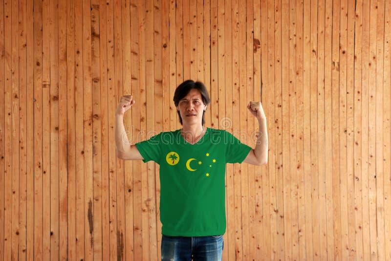 Cor vestindo da bandeira das ilhas de Keeling dos Cocos do homem da camisa e de estar com o punho aumentado no fundo de madeira d fotografia de stock royalty free