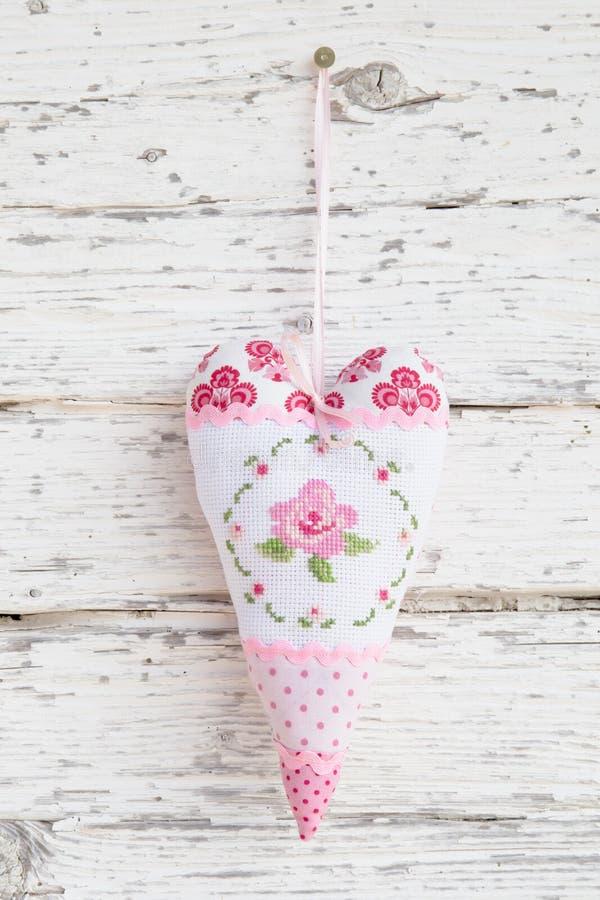 Coração bordado com uma rosa que pendura em um prego para o Ca de cumprimento imagem de stock
