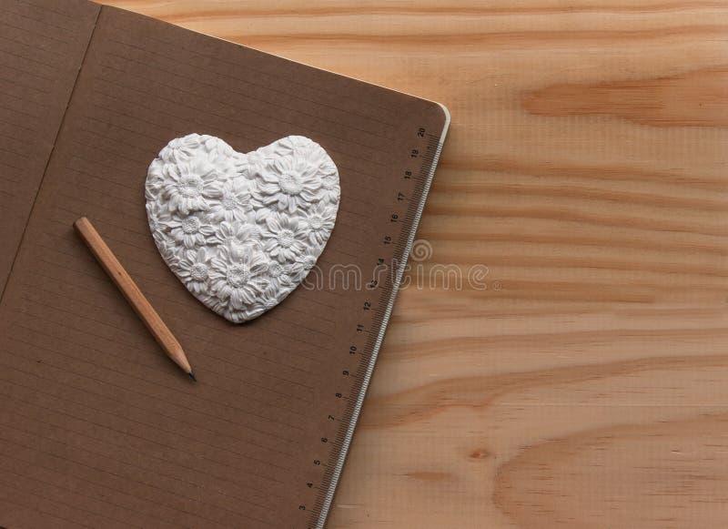 Coração branco que encontra-se no caderno fotografia de stock royalty free