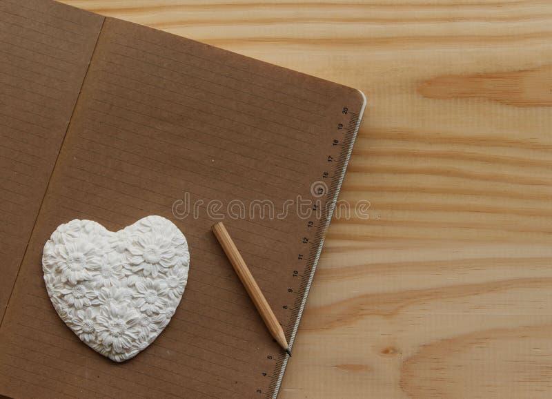 Coração branco que encontra-se no caderno fotografia de stock
