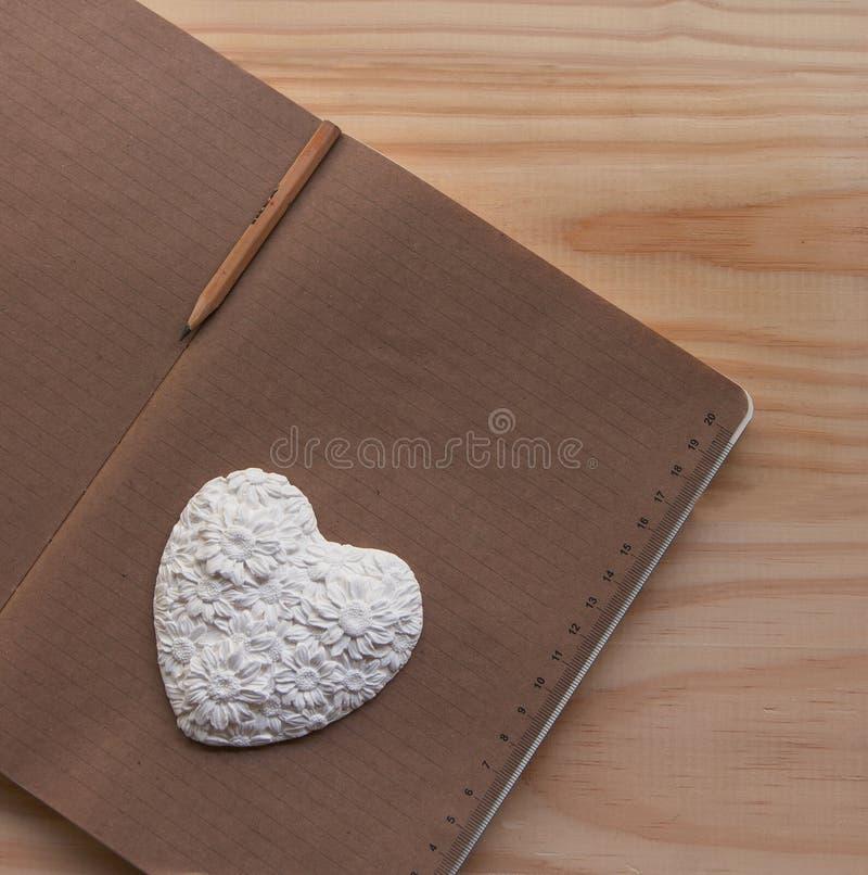 Coração branco que encontra-se no caderno imagens de stock