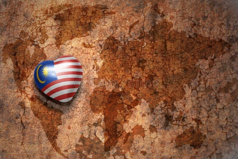 Coração com a bandeira nacional de malaysia em um fundo do papel da quebra do mapa do mundo do vintage fotografia de stock