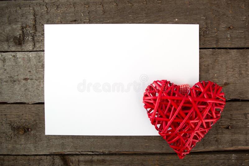 Coração com a folha de papel em uma placa de madeira fotos de stock royalty free