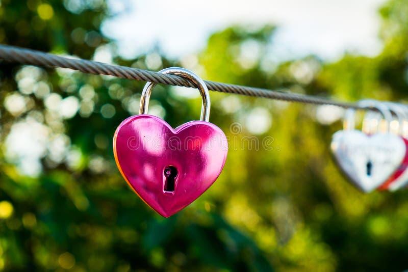 Coração cor-de-rosa o cadeado dado forma do amor está pendurando no fio no fundo do borrão fotos de stock royalty free
