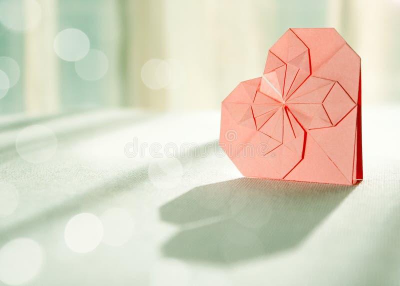 Coração cor-de-rosa Sunlit do papel do origami com sombra na parte dianteira fotografia de stock