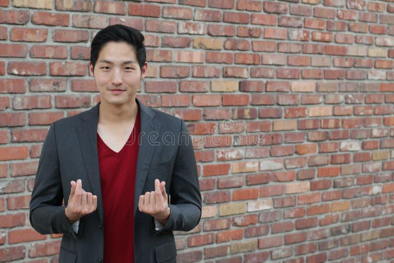 Coração coreano da mão do símbolo, uma mensagem do gesto de mão do amor O homem asiático considerável com as mãos dobrou-se em um imagens de stock