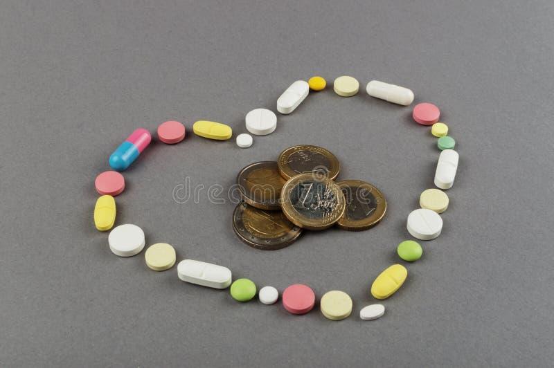 Coração criado dos comprimidos coloridos com o dinheiro Conceito MÉDICO fotografia de stock royalty free