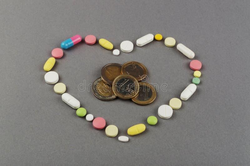 Coração criado dos comprimidos coloridos com o dinheiro Conceito MÉDICO fotos de stock royalty free