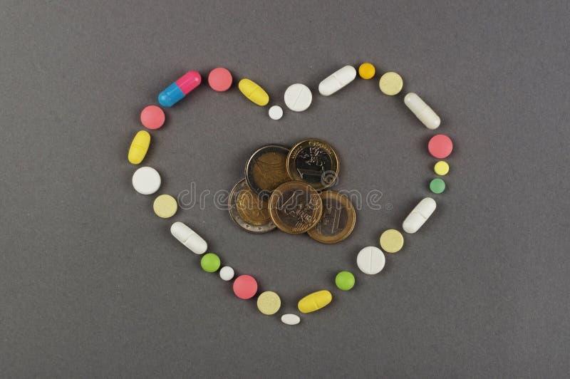 Coração criado dos comprimidos coloridos com o dinheiro Conceito MÉDICO fotografia de stock